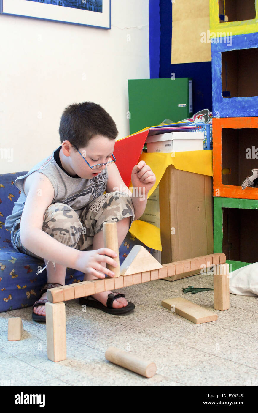 Young boy of 8 building with wooden building blocks in a playroom Stock Photo