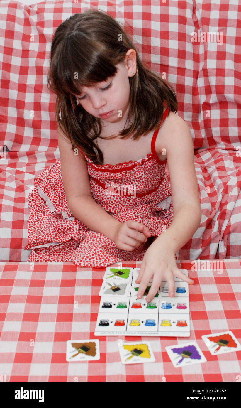 Young preschool girl of 5 Playing with a colour matching game - Stock Image
