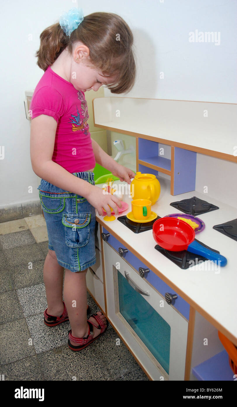 Preschool girl of 5 plays with a toy kitchen - Stock Image