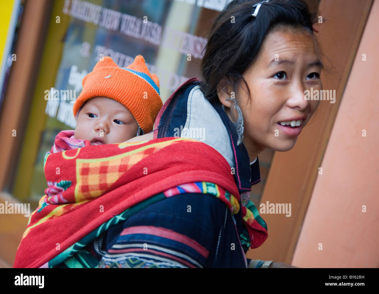 black hmong ethnic woman with a baby. Sapa, Lao Cai province, Vietnam. - Stock Image
