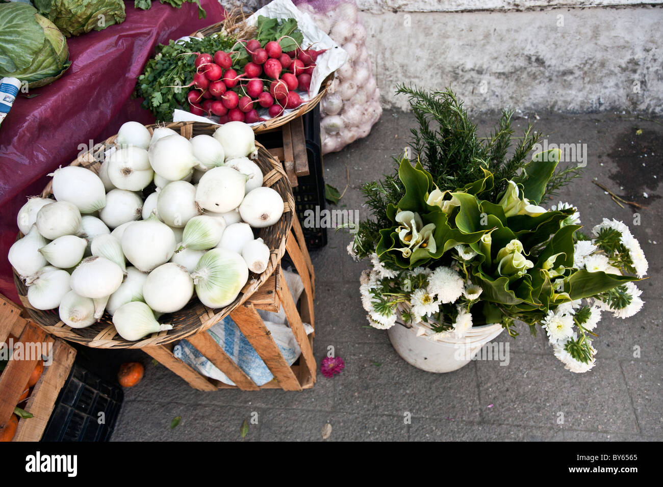 colorful grouping of pure white onions red radishes & calla lilies for sale on main street of Puerto Angel Oaxaca - Stock Image
