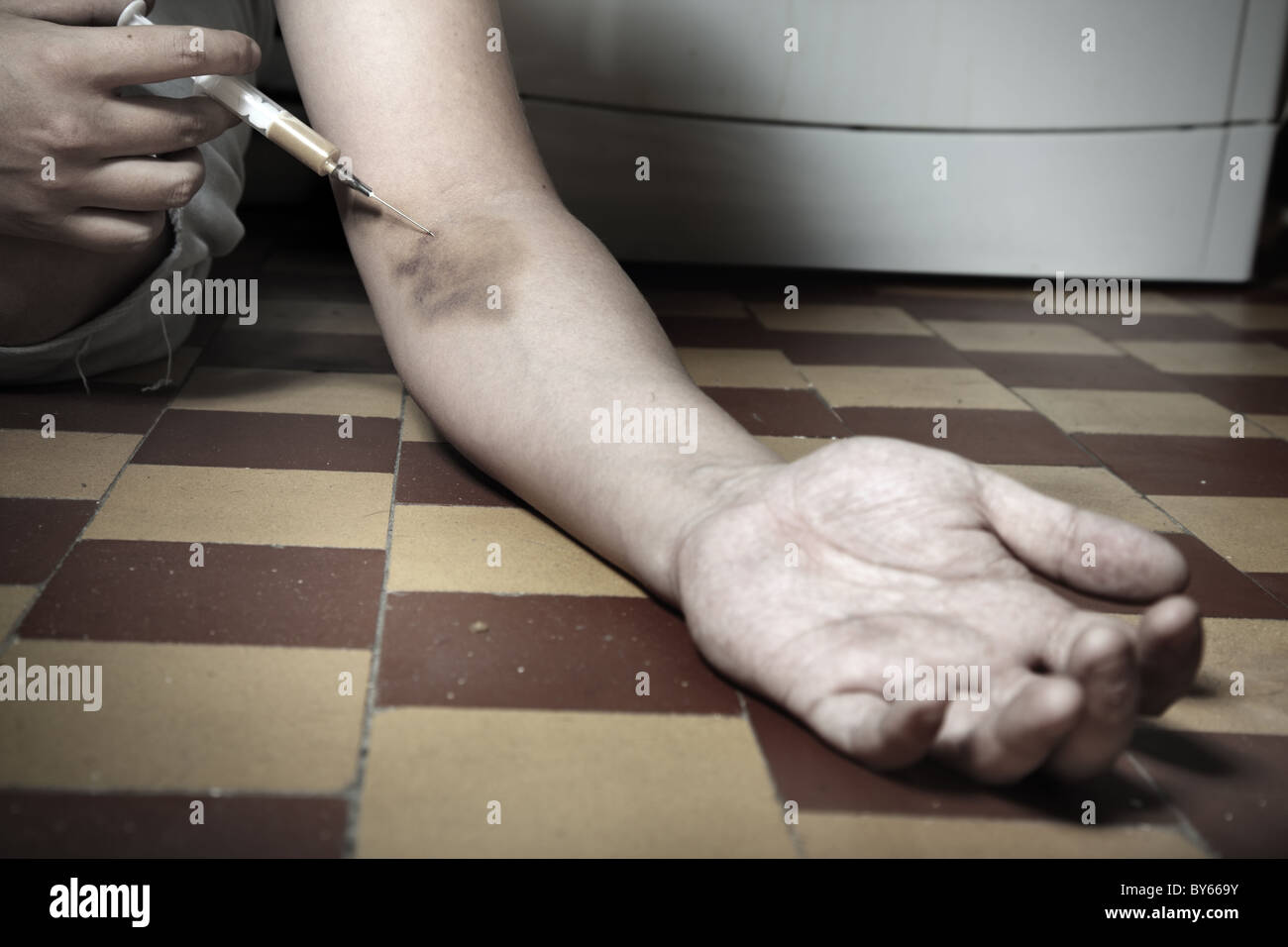 Hand with narcotic syringe on the floor. Artistic colors added - Stock Image