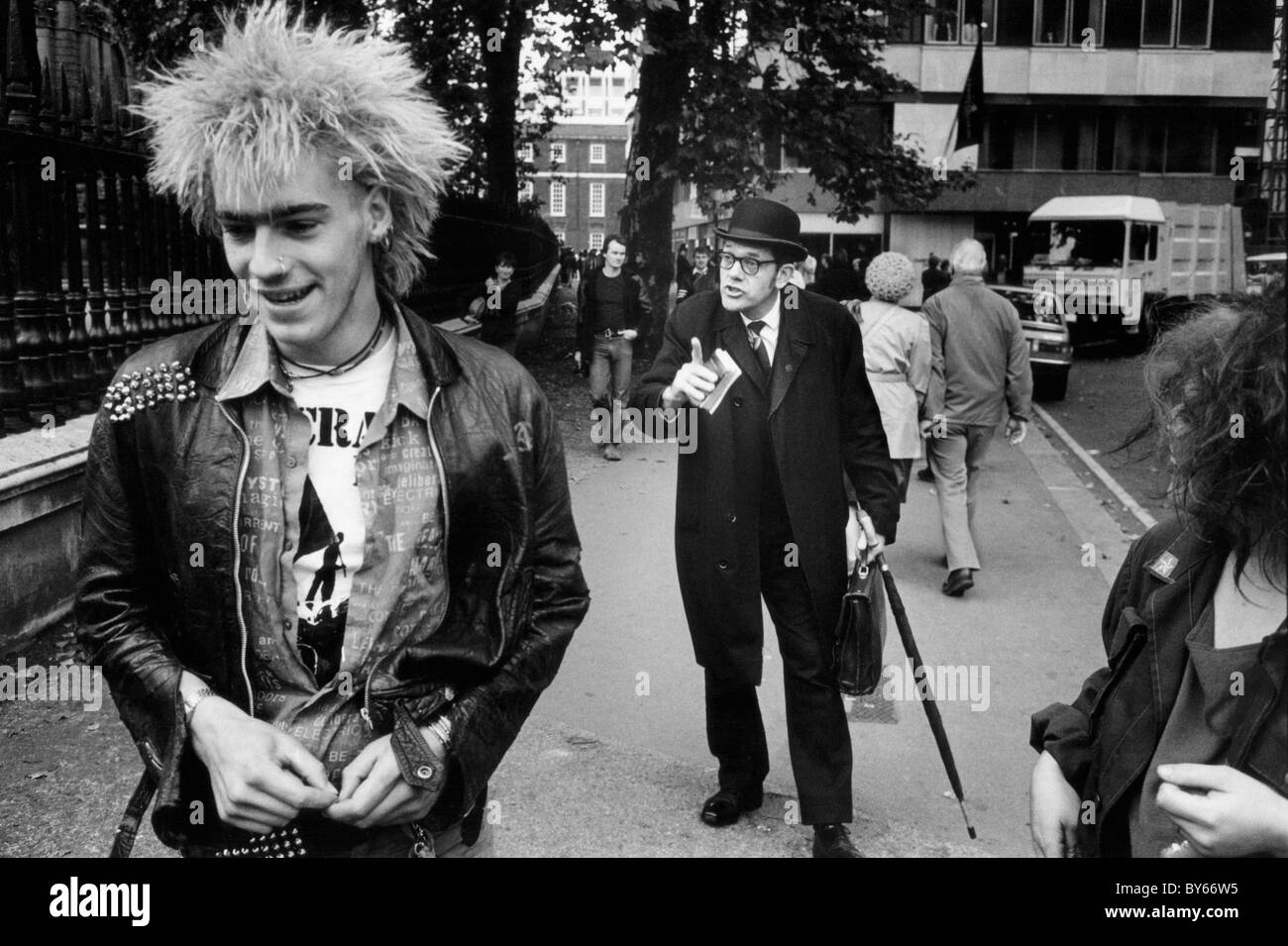 A man who appears to be a city gent scolds a punk in the street near St Paul's Cathedral London - Stock Image