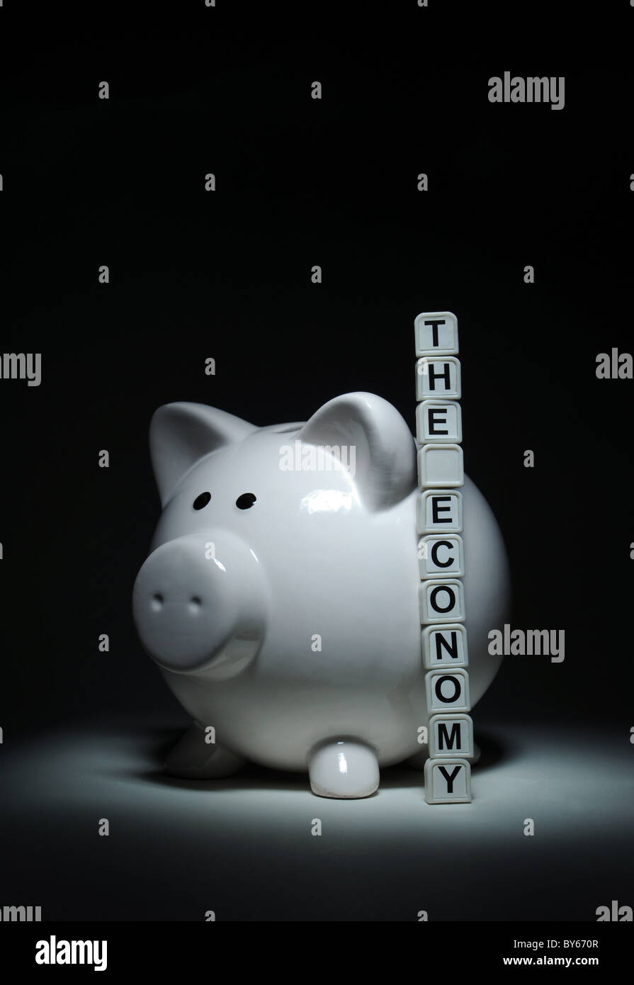 PIGGYBANK WITH WORD TILES SPELLING THE ECONOMY RE ECONOMIC SITUATION BANKS MORTGAGES HOMES FINANCES  SAVINGS HOUSEHOLD - Stock Image