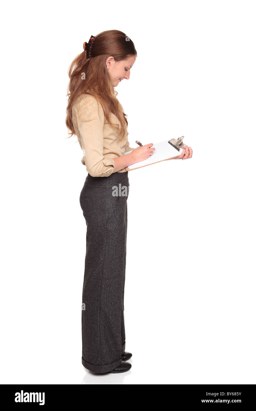 Isolated studio shot of a Caucasian businesswoman taking notes on a clipboard - Stock Image