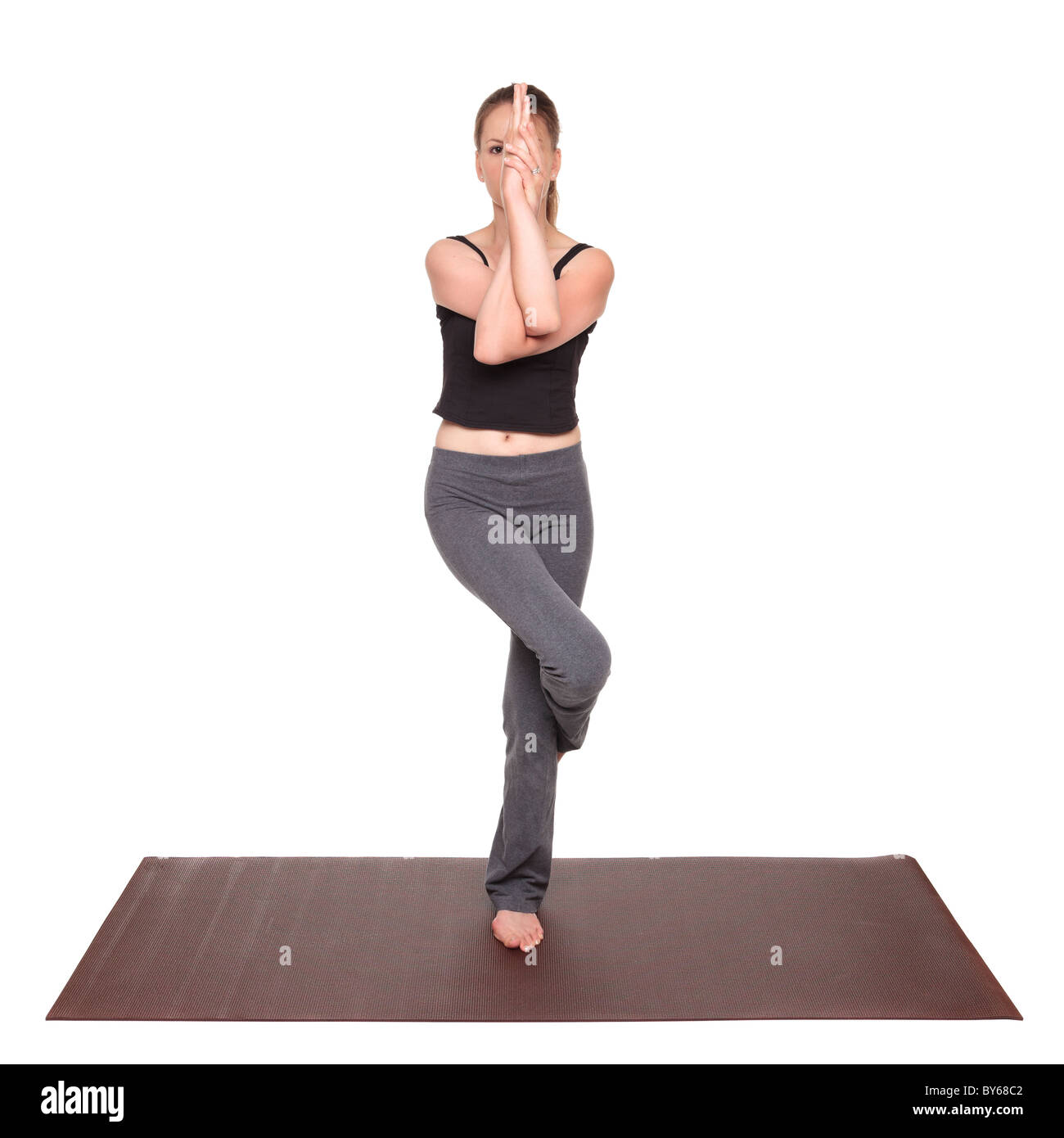 Isolated studio shot of a fit Caucasian woman holding the garudasana Eagle Pose yoga position on an exercise mat. - Stock Image