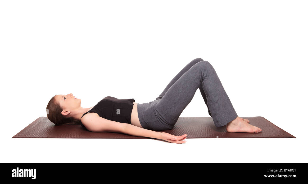 Isolated studio shot of a fit Caucasian woman warming up with a pelvic tilt exercise - Stock Image