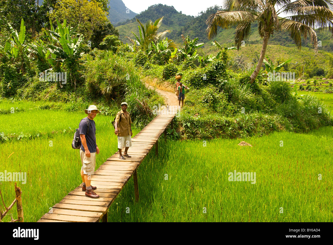 Tourist and park guide walking to the entrance to Marojejy National Park in northeast Madagascar. - Stock Image
