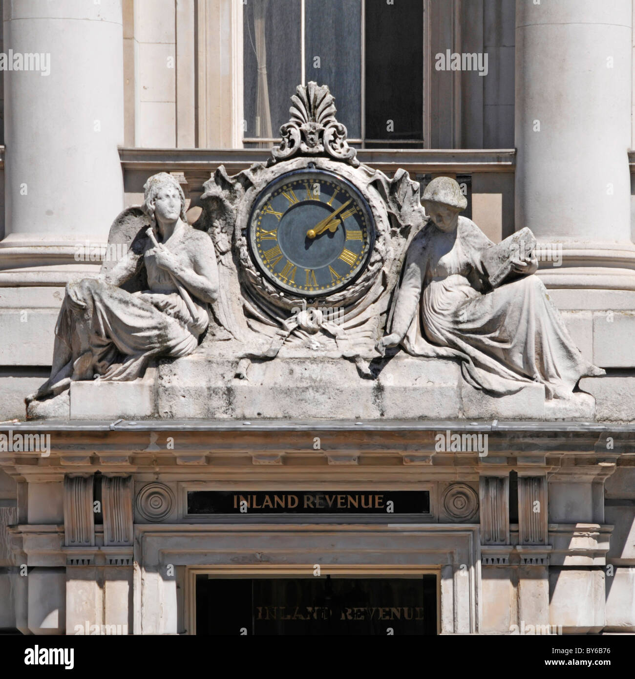 Close up of Inland Revenue sign above Lancaster Place entrance to Somerset House with clock & two female stone - Stock Image