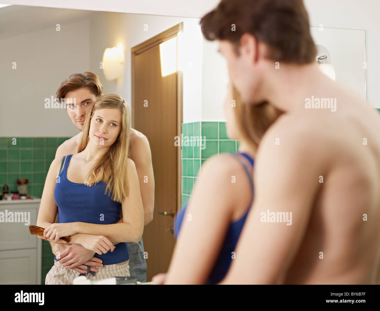 Husband Hugging Wife In Bathroom And Looking At Mirror Horizontal