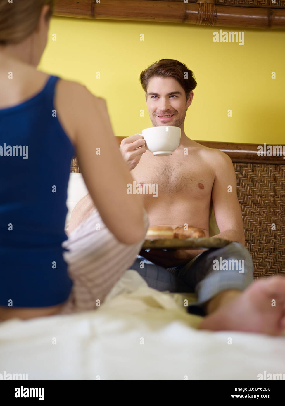caucasian heterosexual couple eating croissant and drinking coffee in bed. Vertical shape, rear view, focus on background Stock Photo