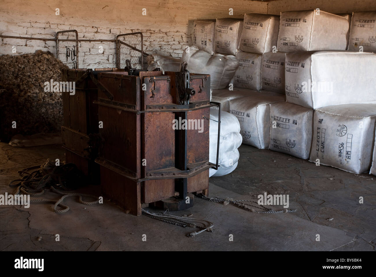 A wooden wool press and bales of wool in a shearing shed. - Stock Image