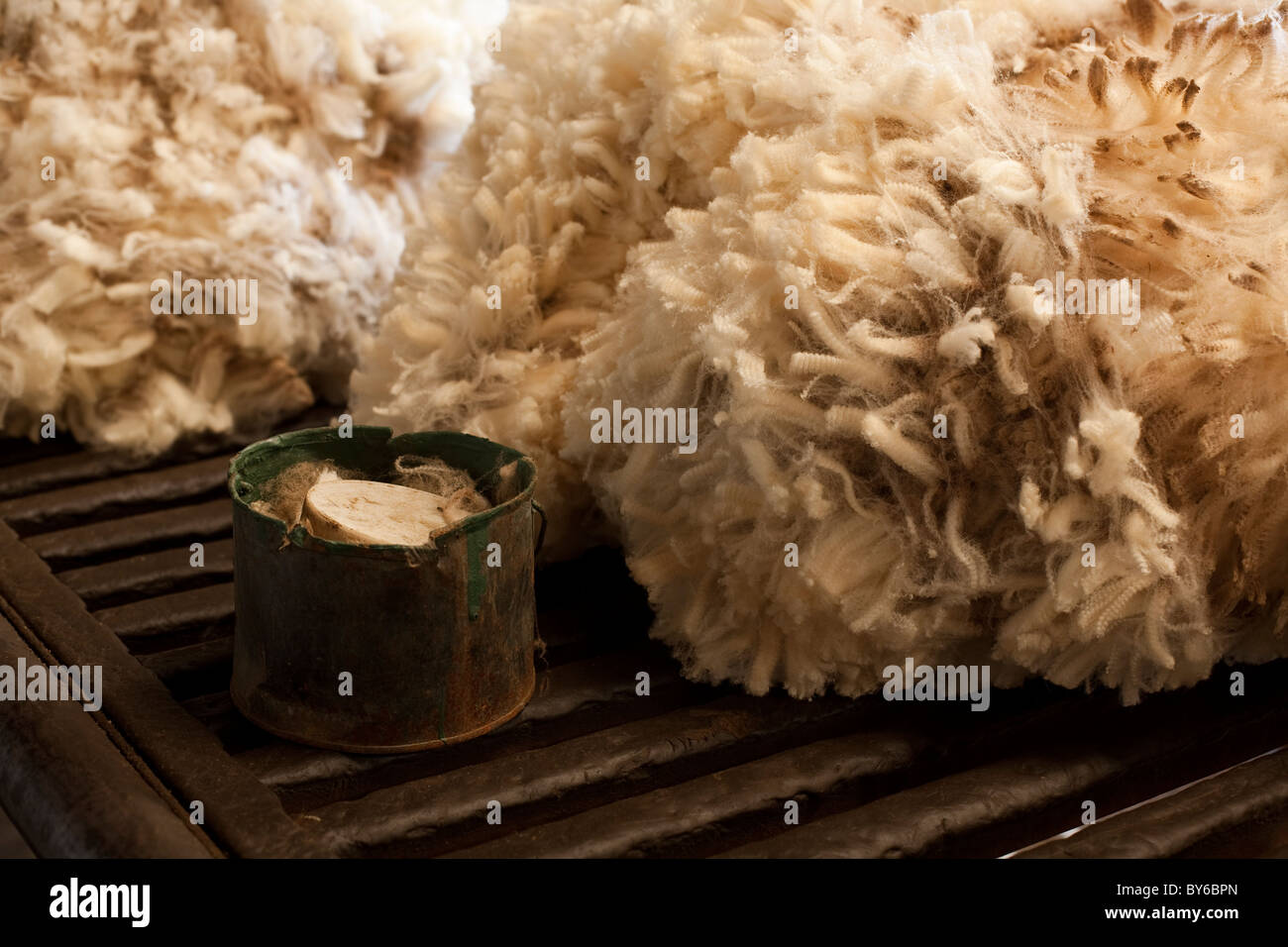 A fleece and a tin on a wool table in a shearing shed. - Stock Image