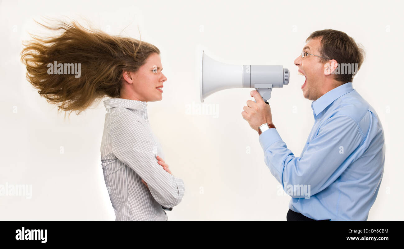 Image of strict boss shouting at businesswoman through loudspeaker so loudly that her hair being blown by strong Stock Photo
