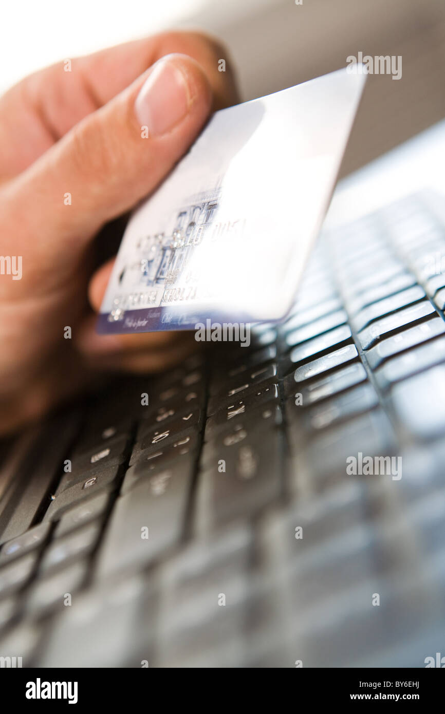 Close-up of human hand holding plastic card over black keyboard - Stock Image