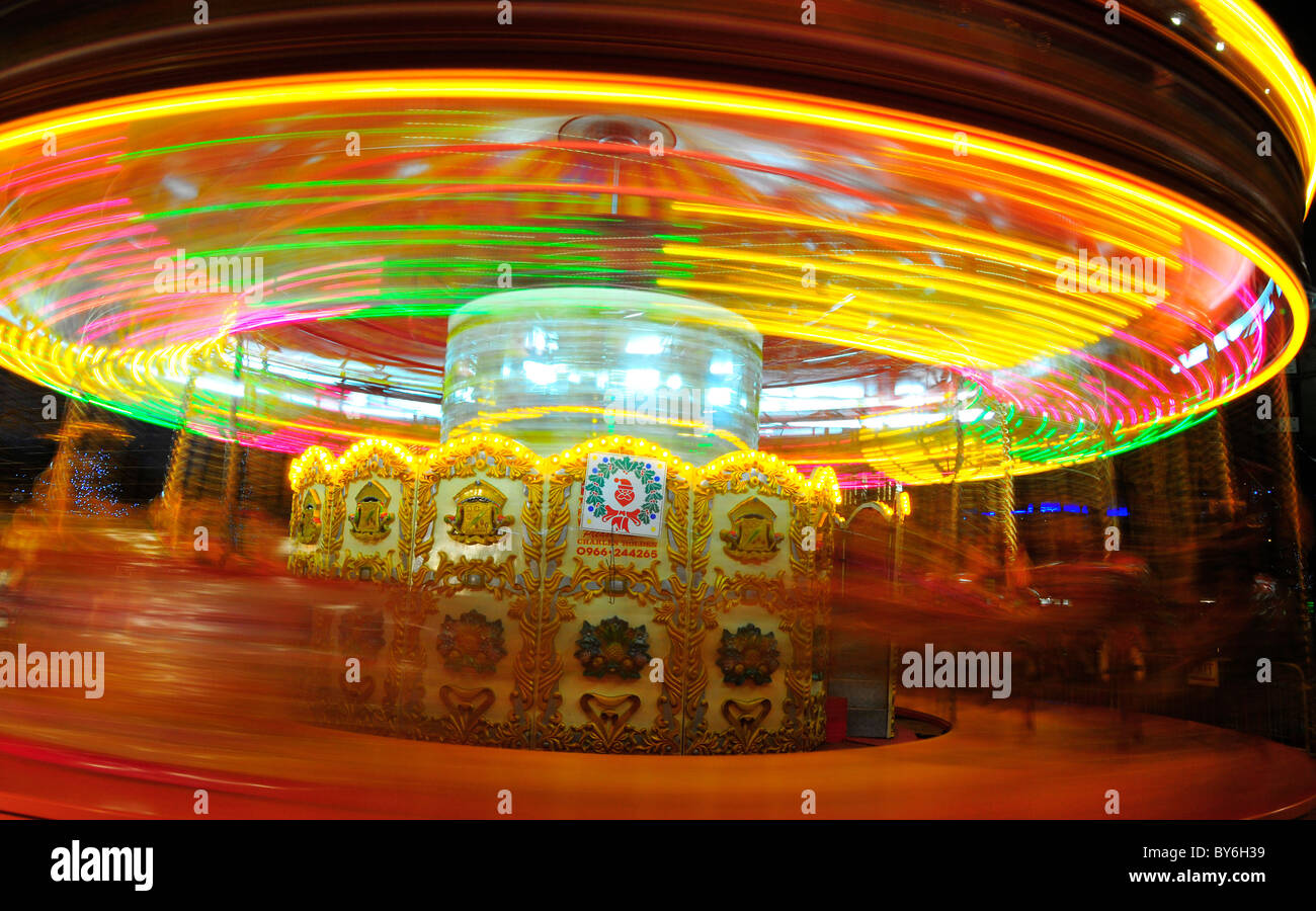 Funfair rides by night with light trails - Stock Image