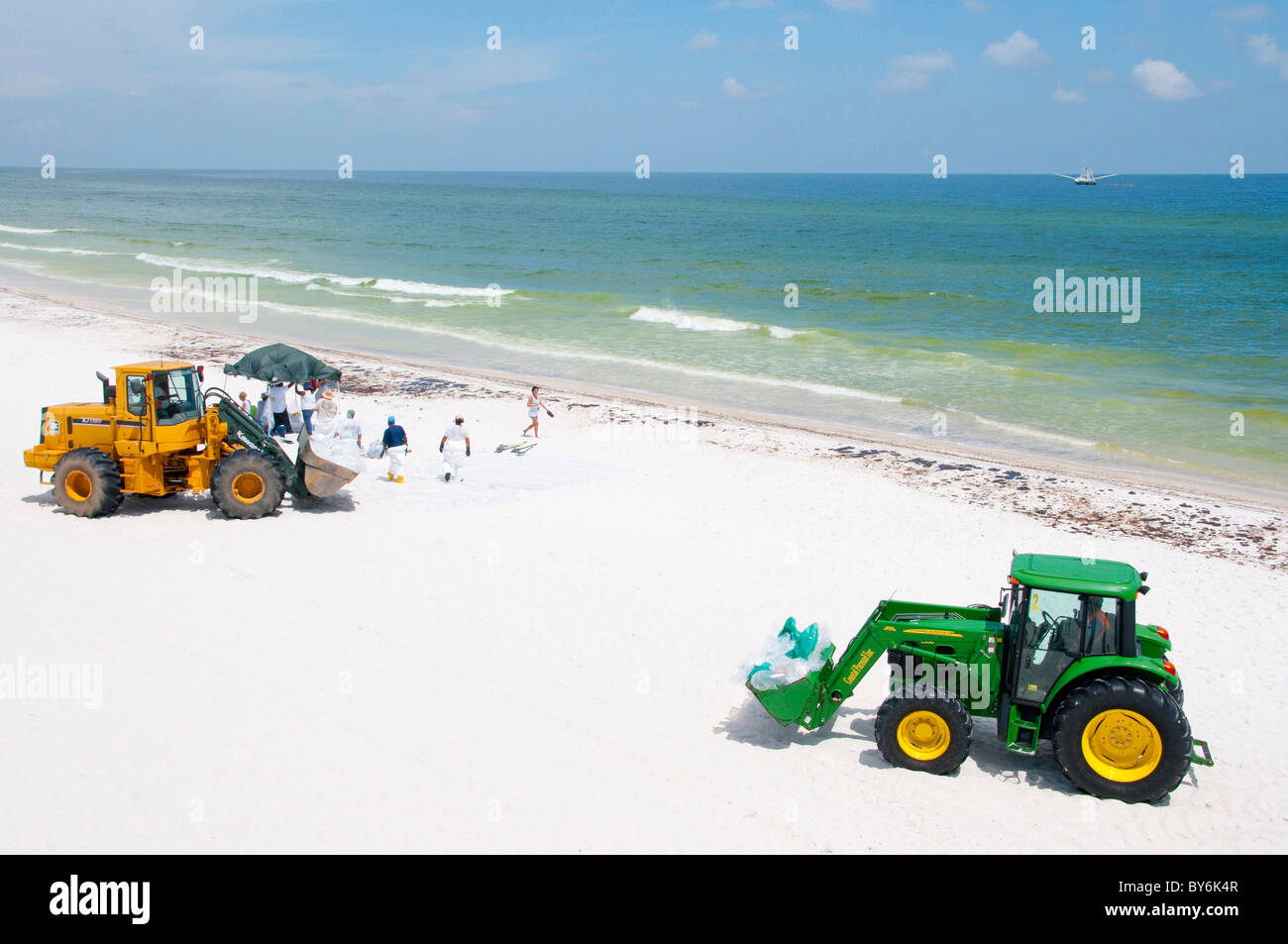 Heavy machinery drives on deserted Pensacola beach to help remove oil at the peak of tourist season - Stock Image