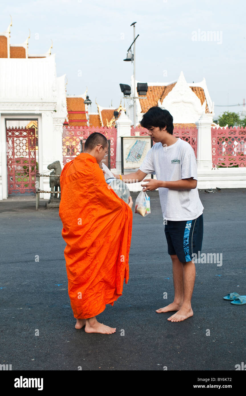 Monk receives alms from a young merit-maker in front of Wat Benjamabophit, Bangkok, Thailand Stock Photo