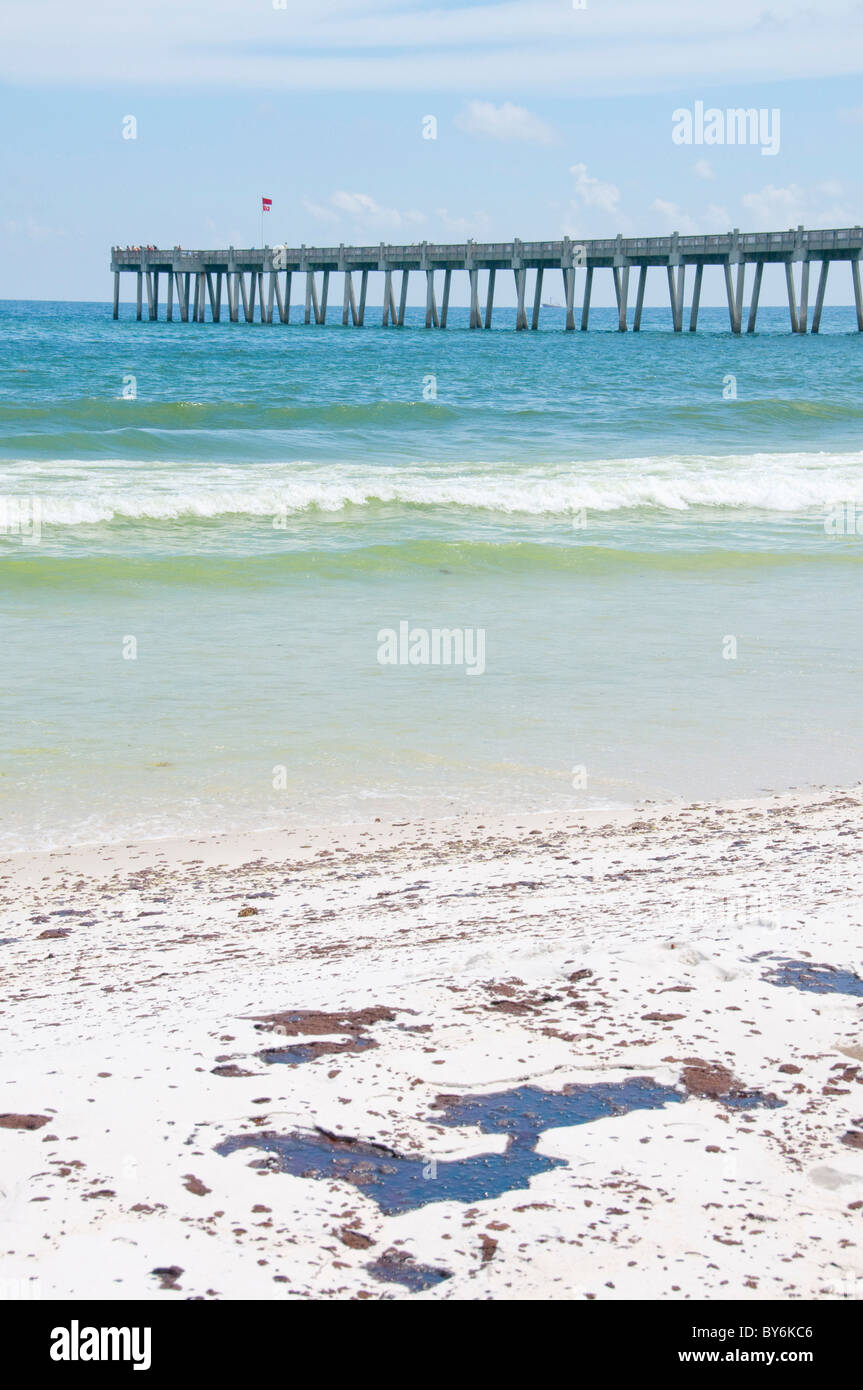 Pools of oil wash ashore on Pensacola Beach - Stock Image