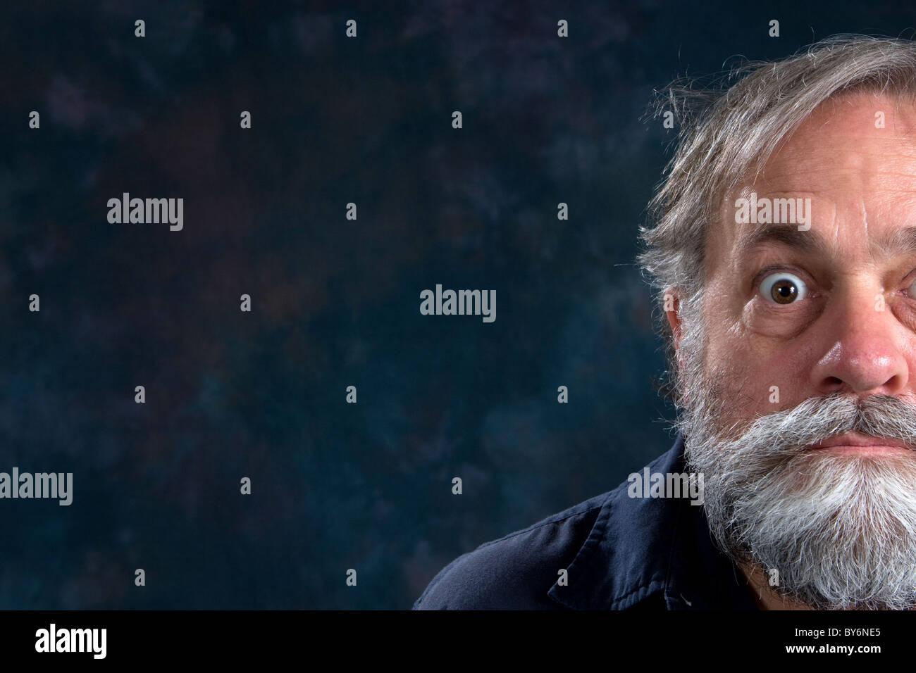 Half the face of a bug eyed mature man with beard. - Stock Image