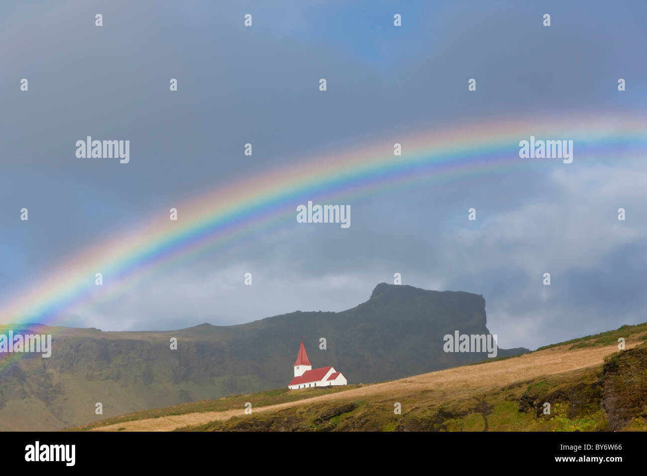 Rainbow over church, Vik, Iceland - Stock Image