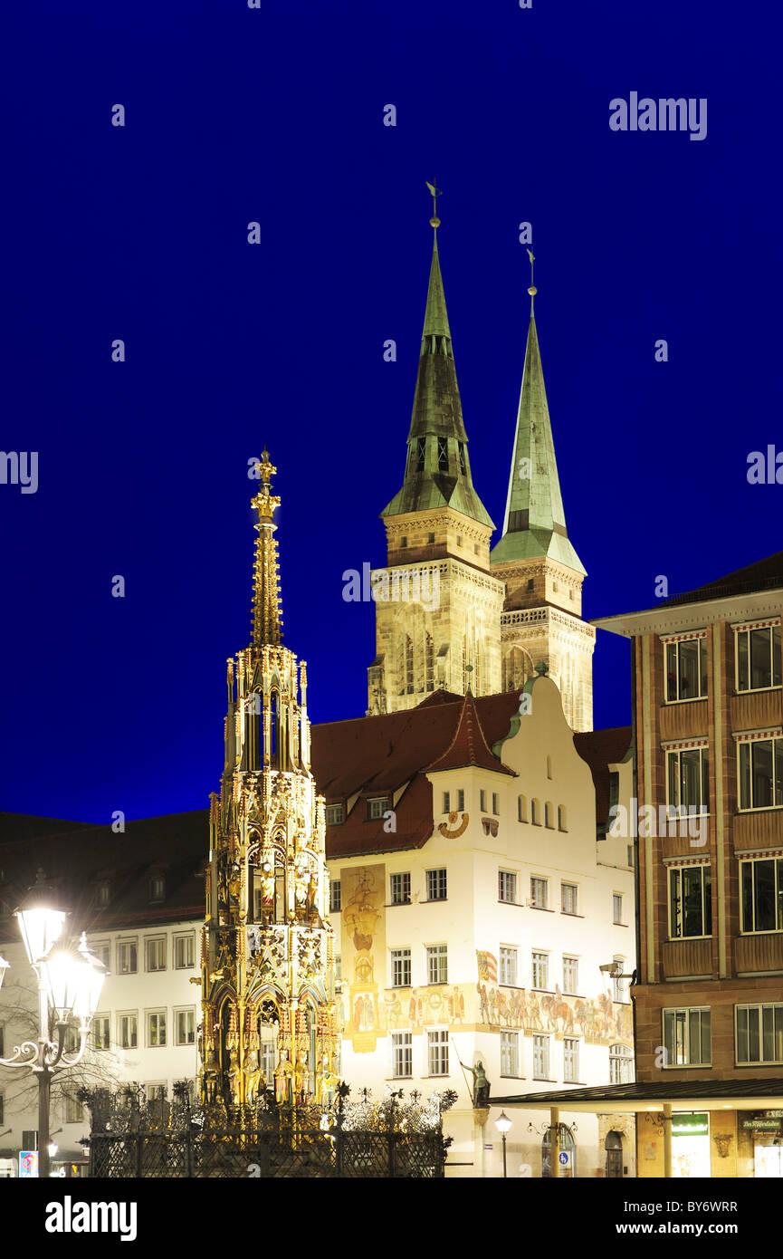 Illuminated fountain Schoener Brunnen on the market square and St. Sebaldus church at night, Nuremberg, Bavaria, - Stock Image