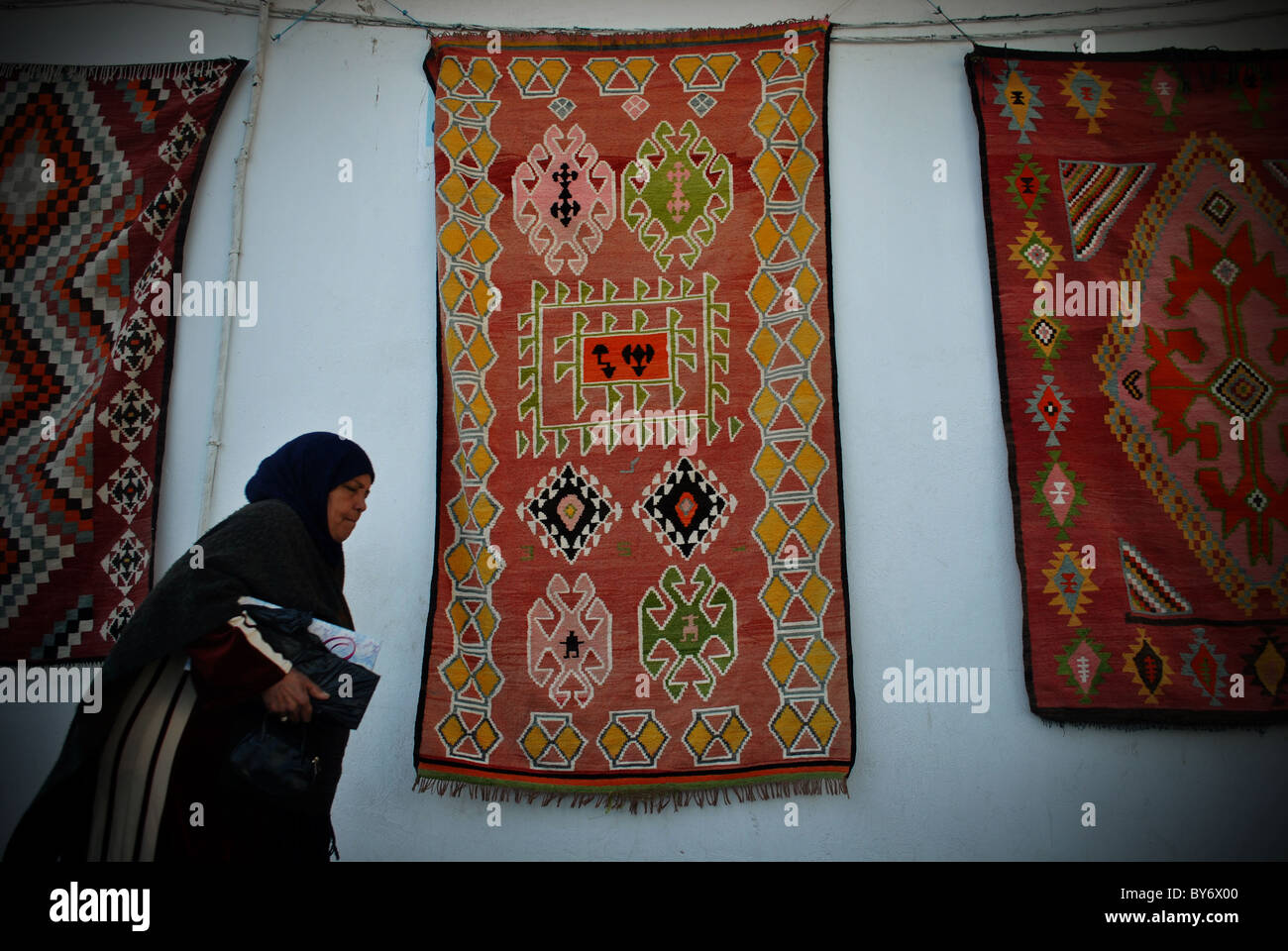Woman walking past rugs in Sousse, Tunisia - Stock Image
