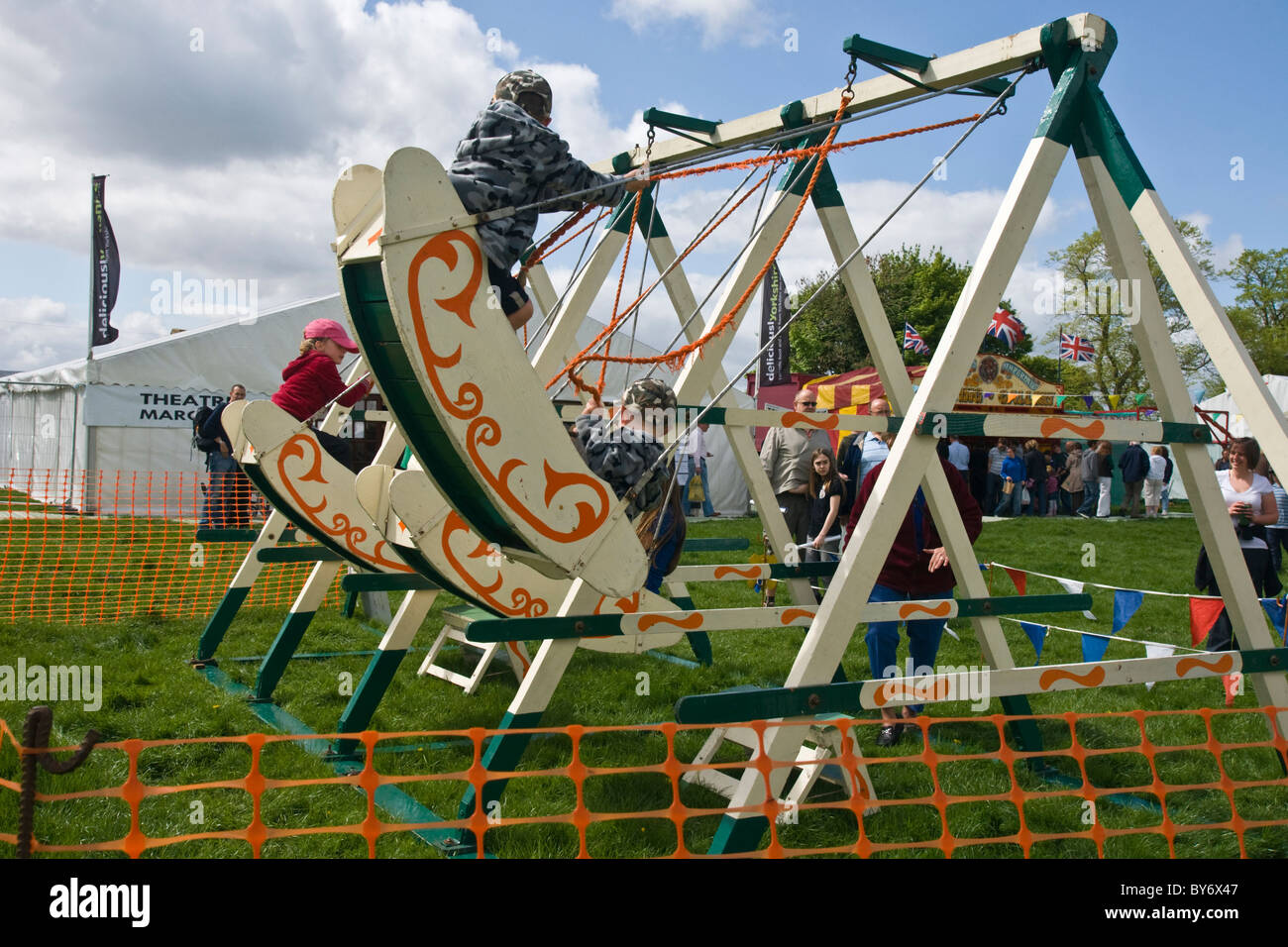 Children playing on boat swings at the annual Festival of Food and Drink at Leyburn in North Yorkshire - Stock Image