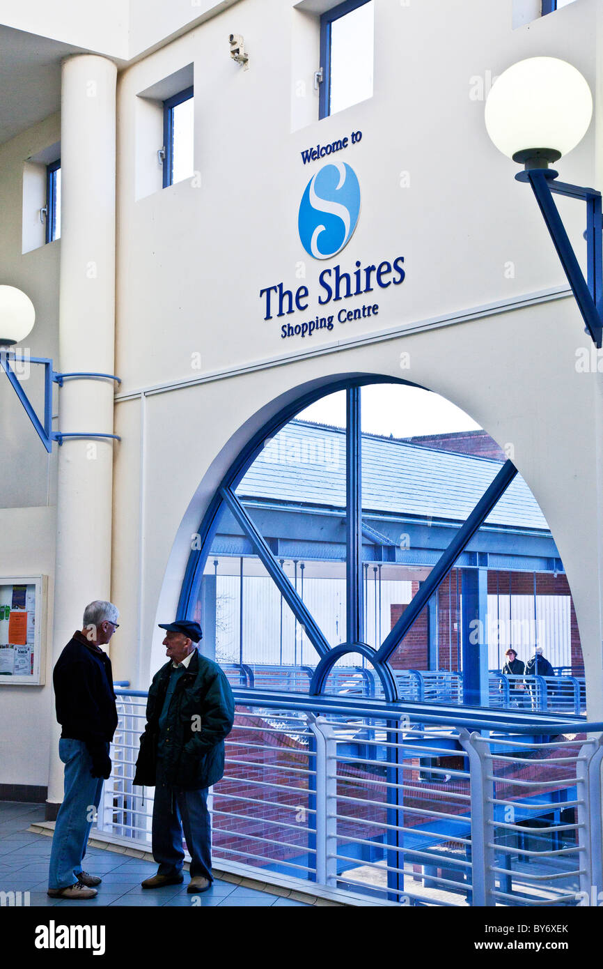 Two elderly men chatting near the entrance to a shopping mall or centre in England, UK - Stock Image