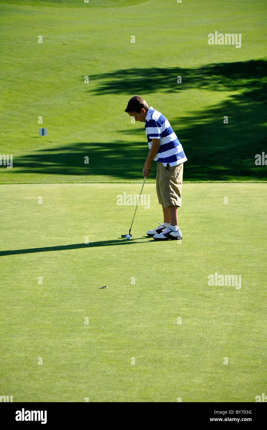 Young ball ready to putt a golf ball on a golf course.  The photo was taken in the late afternoon. - Stock Image
