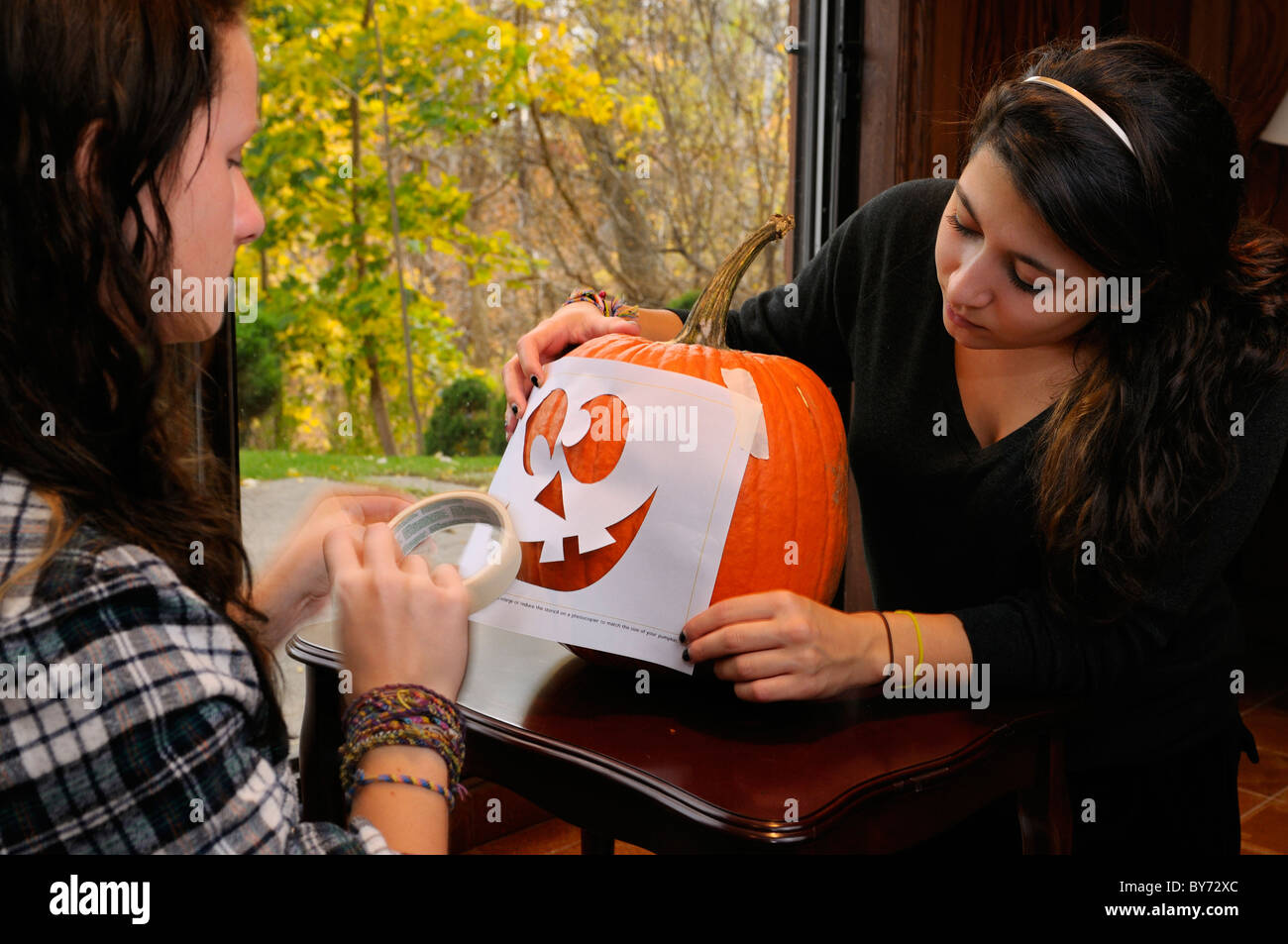 Two teenage girls applying a stencil of a face onto a pumpkin for carving a Halloween Jack O Lantern - Stock Image