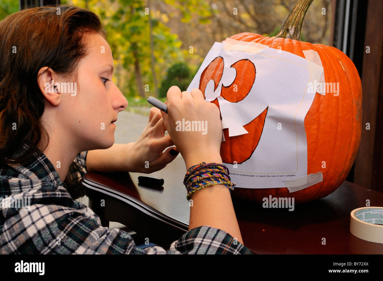 Young teenage girl carefully tracing a face pattern onto a pumpkin for Halloween - Stock Image