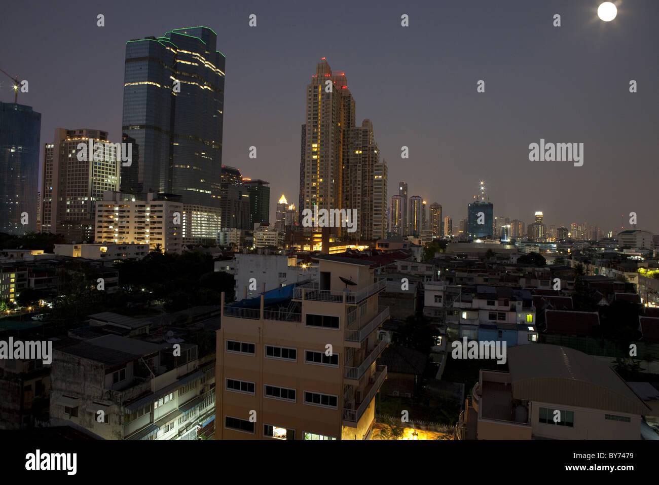 Full moon over Sathorn business area, Bangkok, Thailand - Stock Image