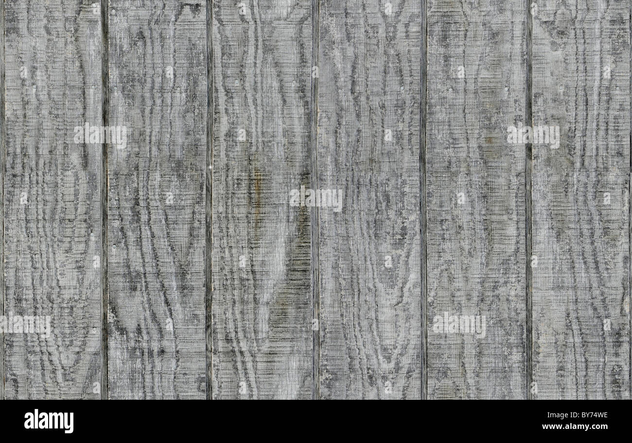 Weathered gray wooden barn siding using vertical planks - Stock Image