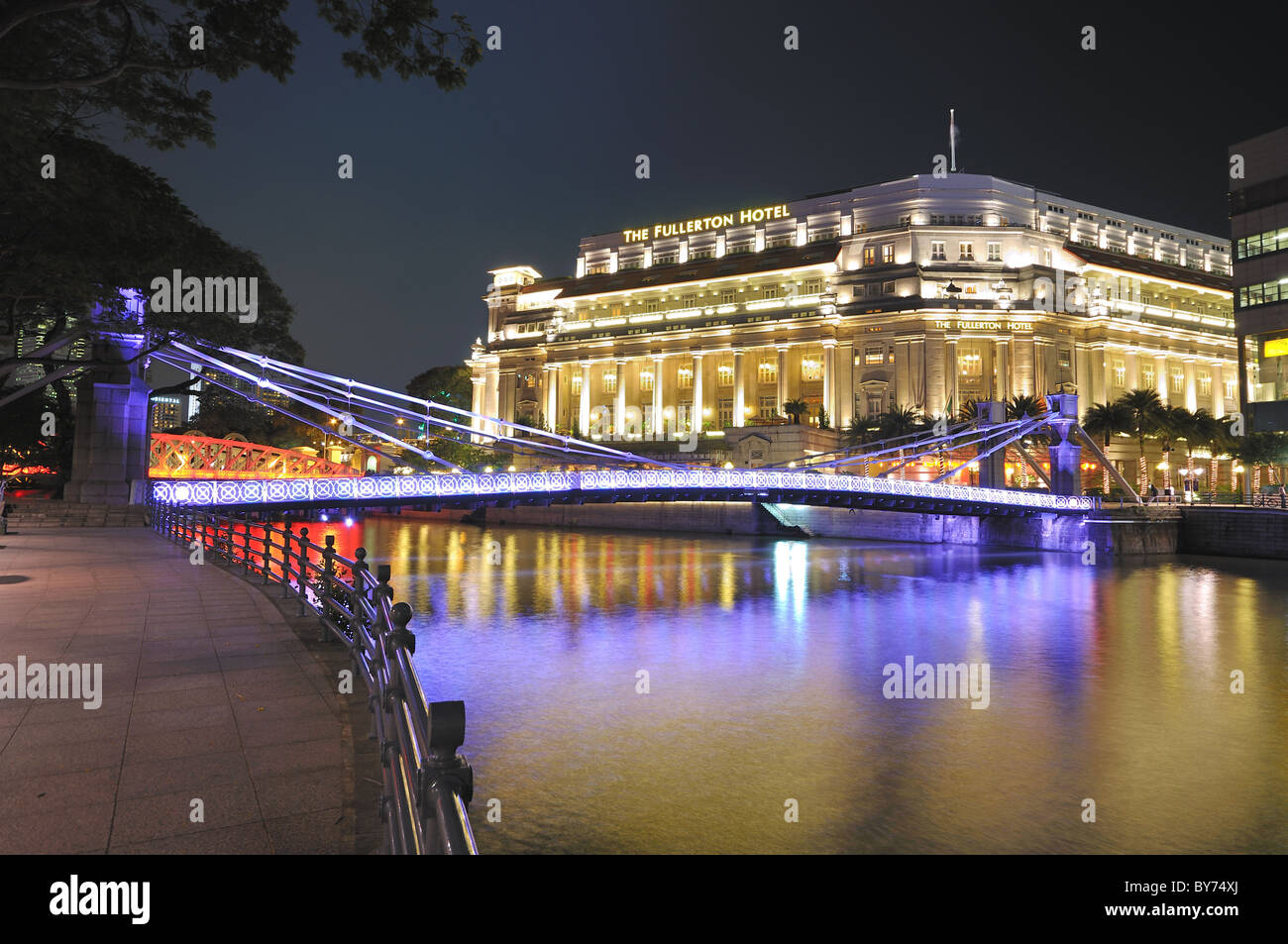 The Fullerton Hotel and the Cavenagh Bridge aglow in festive lights. - Stock Image