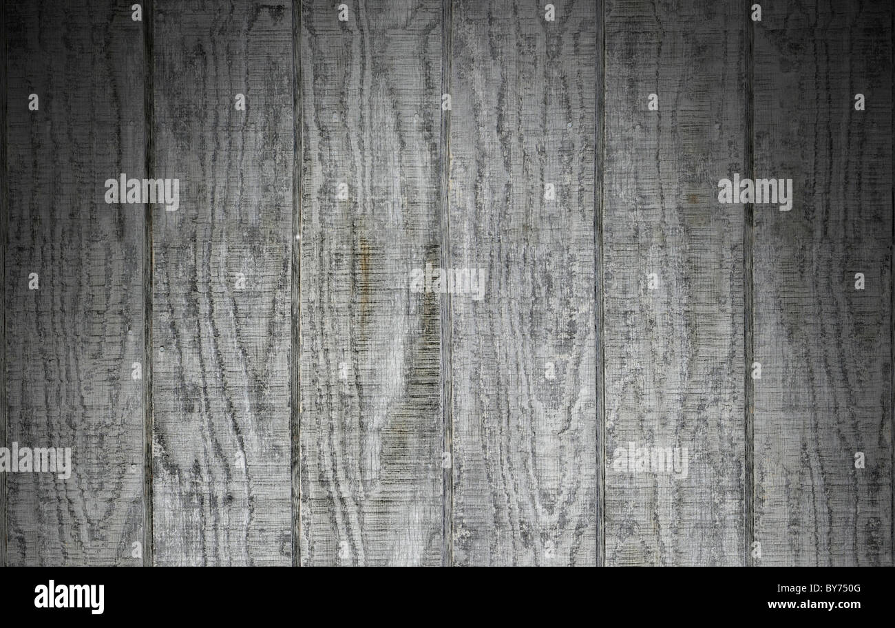Weathered gray wooden barn siding using vertical planks lit dramatically from above - Stock Image