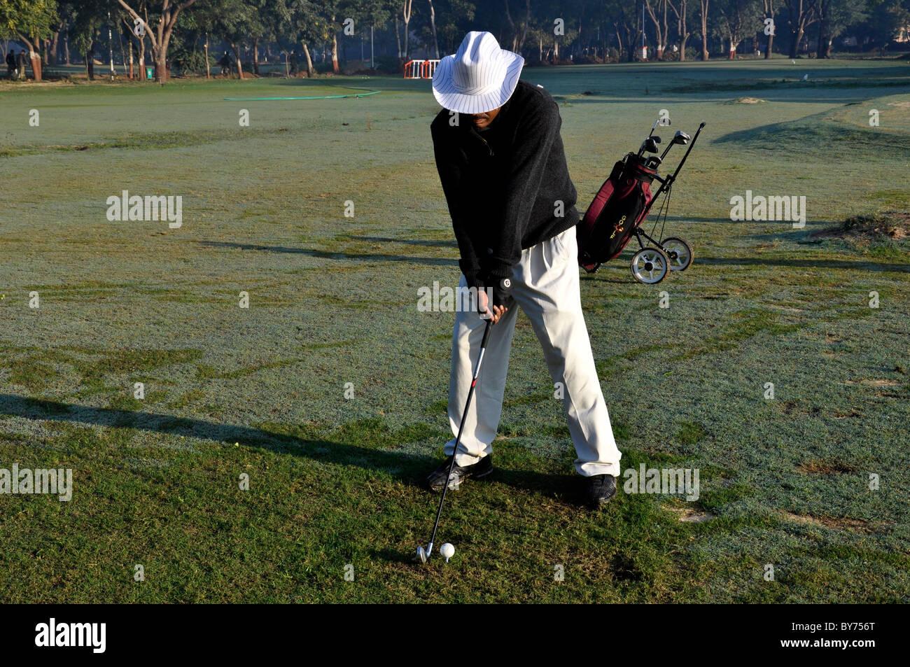 A golfer making tee shot - Stock Image