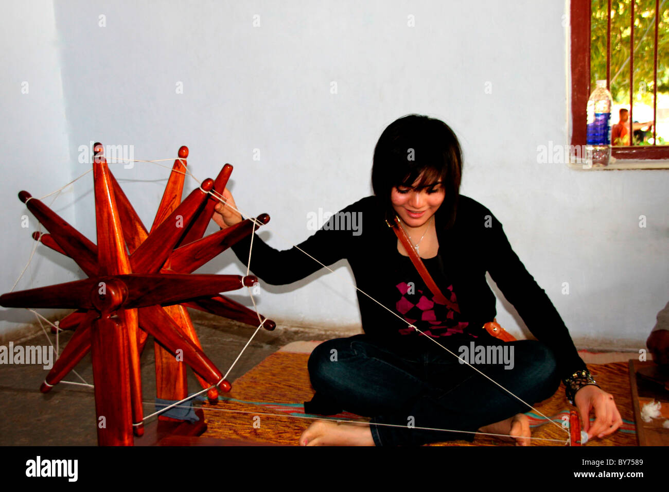 A girl using spinning wheel Stock Photo