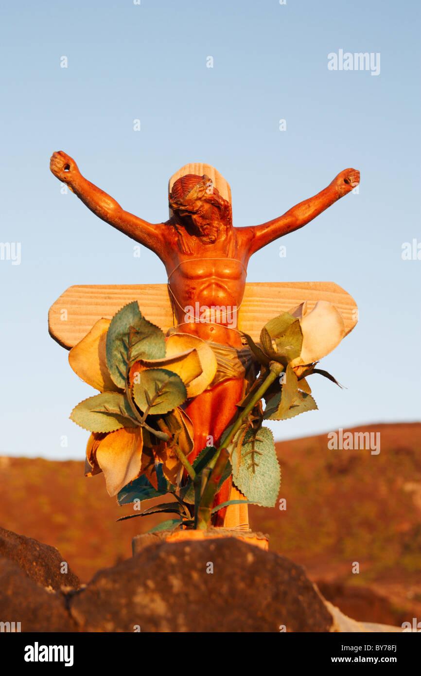 Jesus on wooden cross on makeshift grave on beach in Spain - Stock Image