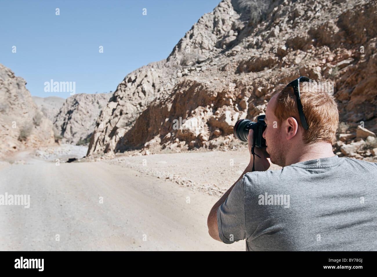 Tourist taking Photograph in Wadi Bih, Oman - Stock Image