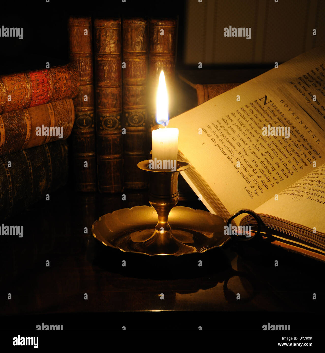 Antiquarian books lit by candlelight - Stock Image