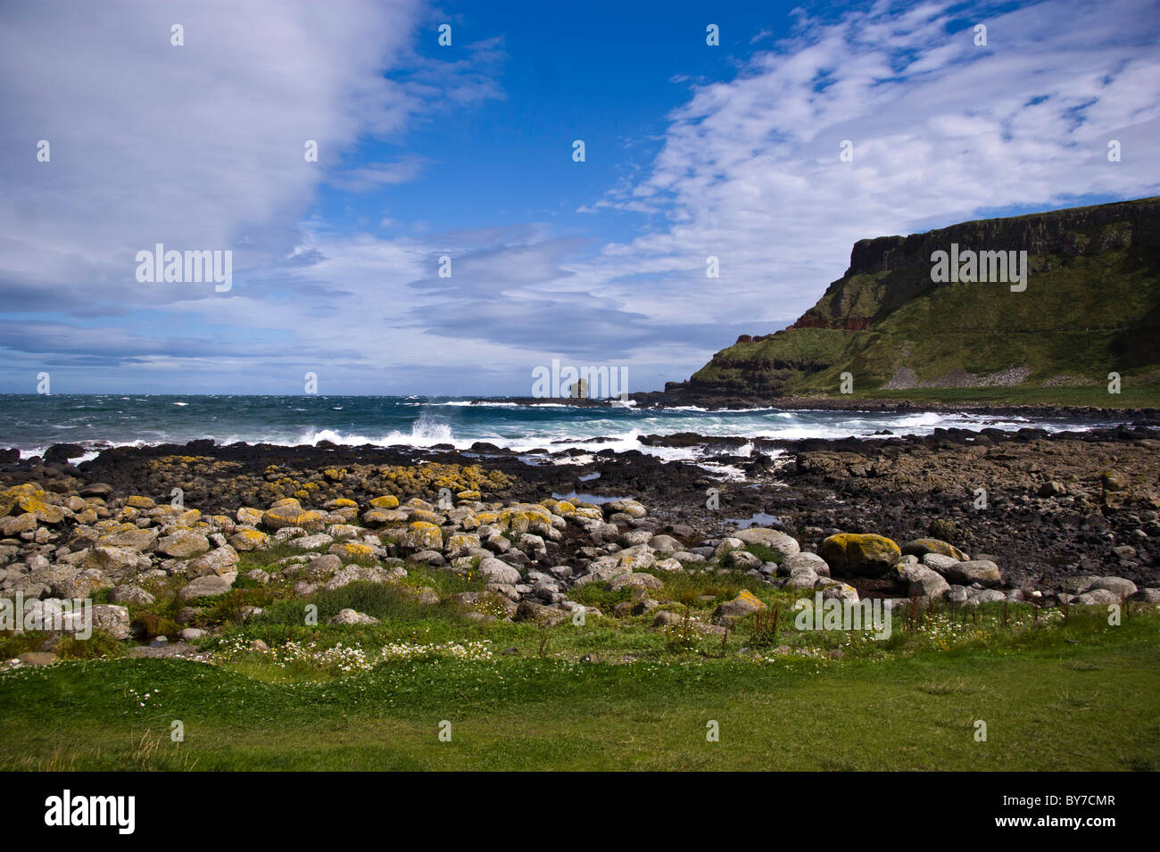 Giant's Causeway, Northern Ireland, County Antrim in a sunny day with blue sky and waves crashing on the rocks - Stock Image