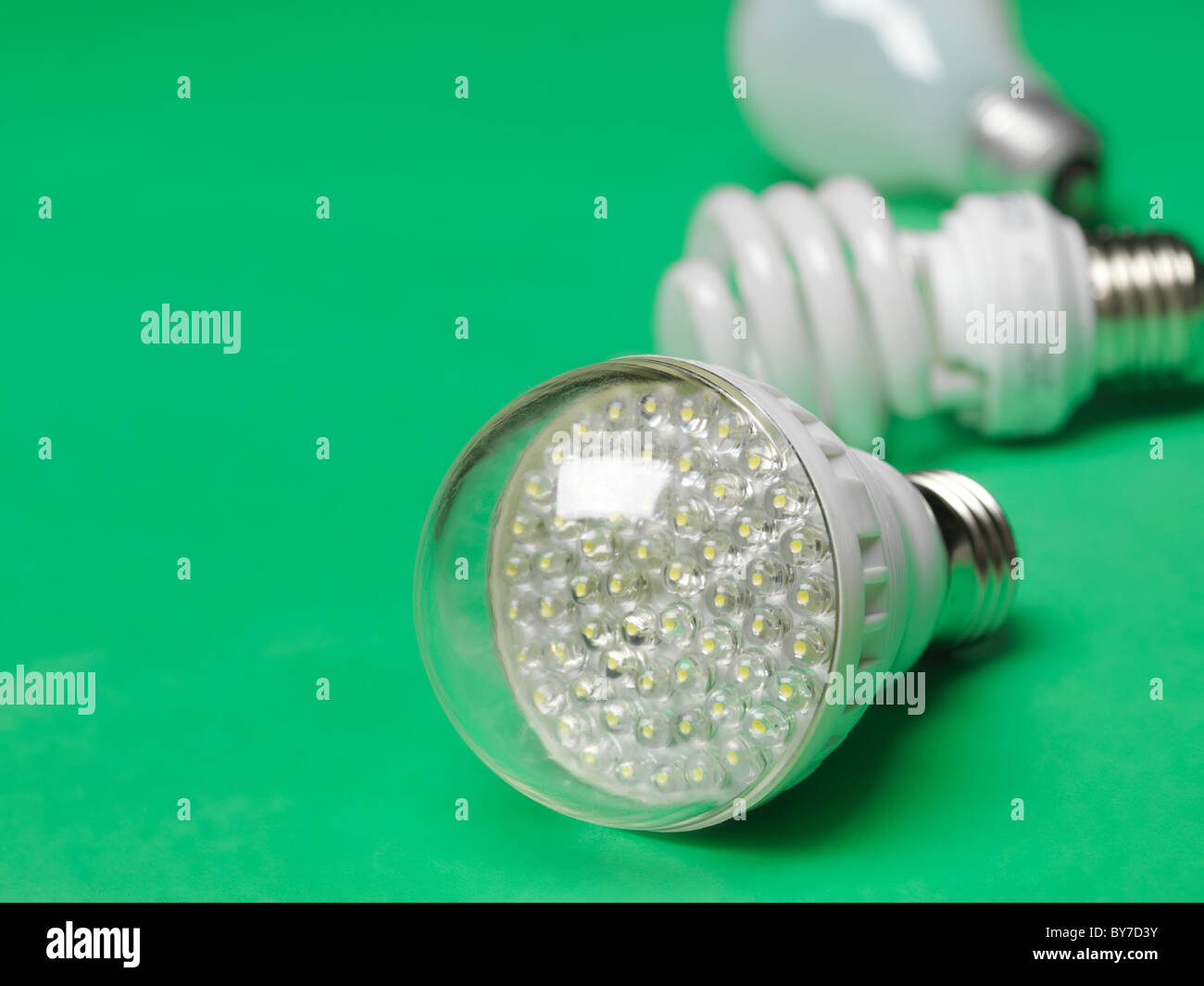 LED light bulb with fluorescent and incandescent bulbs in the background, showing three generations of light bulbs - Stock Image