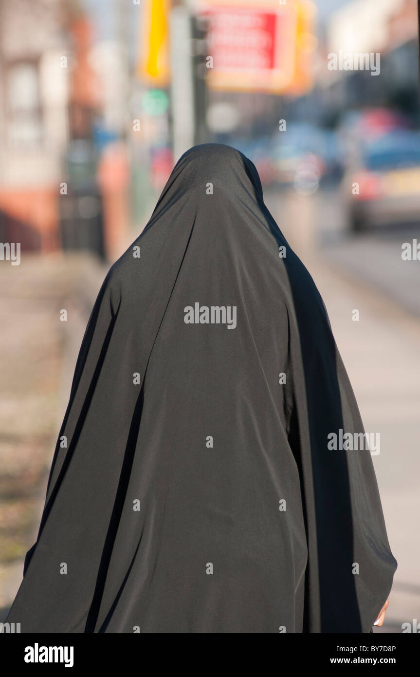A Muslim woman wearing a Burka walks down Stoney Stanton Rd in Coventry, West Midlands, England - Stock Image