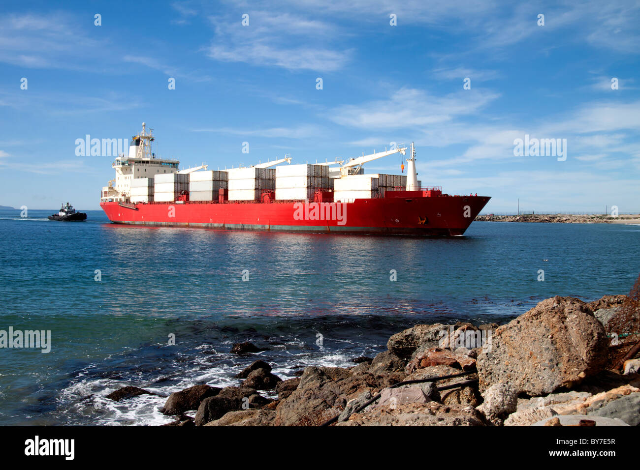 Cargo ship being guided by tugboat through the harbor - Stock Image