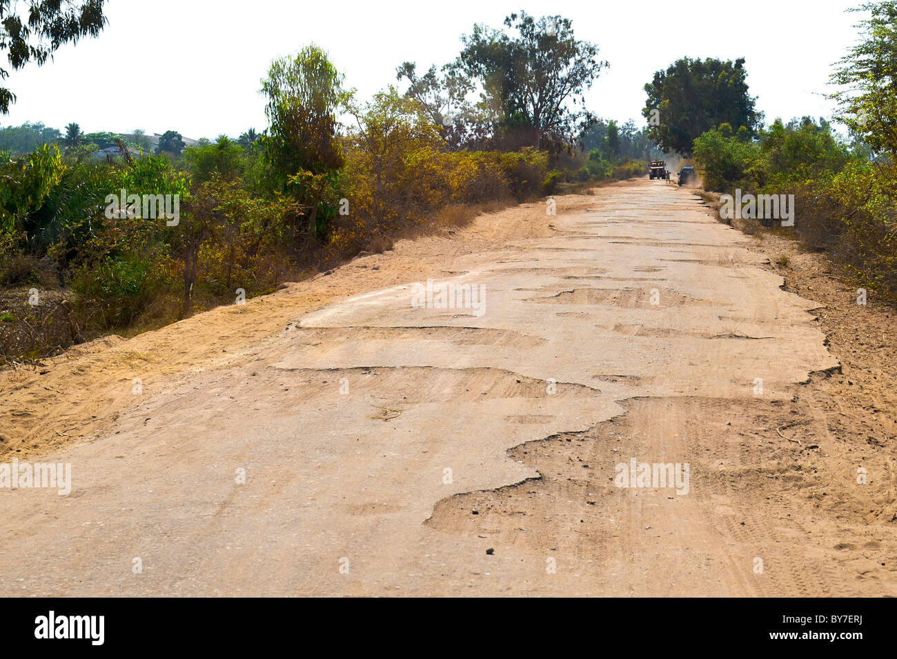 The dilapidated tar road leading out of the town of Morondava on the southwestern coast of Madagascar. - Stock Image