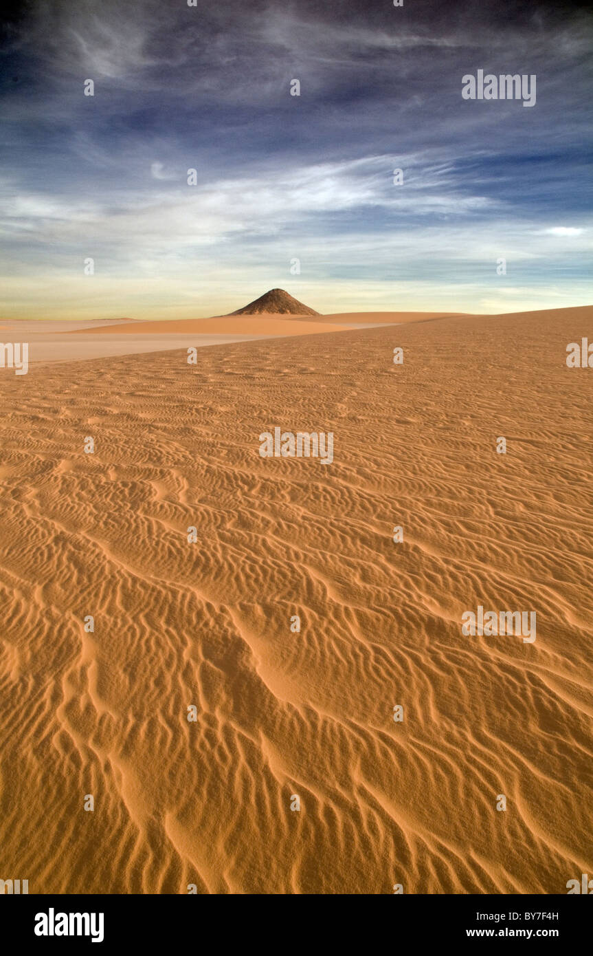 A cone-shaped volcanic rock formation juts out of the sand in the Gilf Kebir region of Egypt's Western Desert. - Stock Image