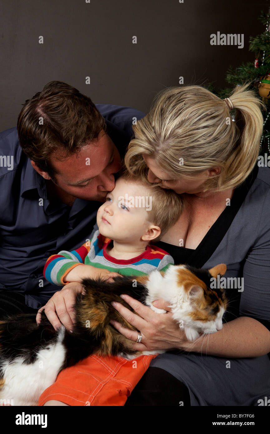 Family love, Mother and father kiss their toddler son on the head while he holds the pet cat - Stock Image