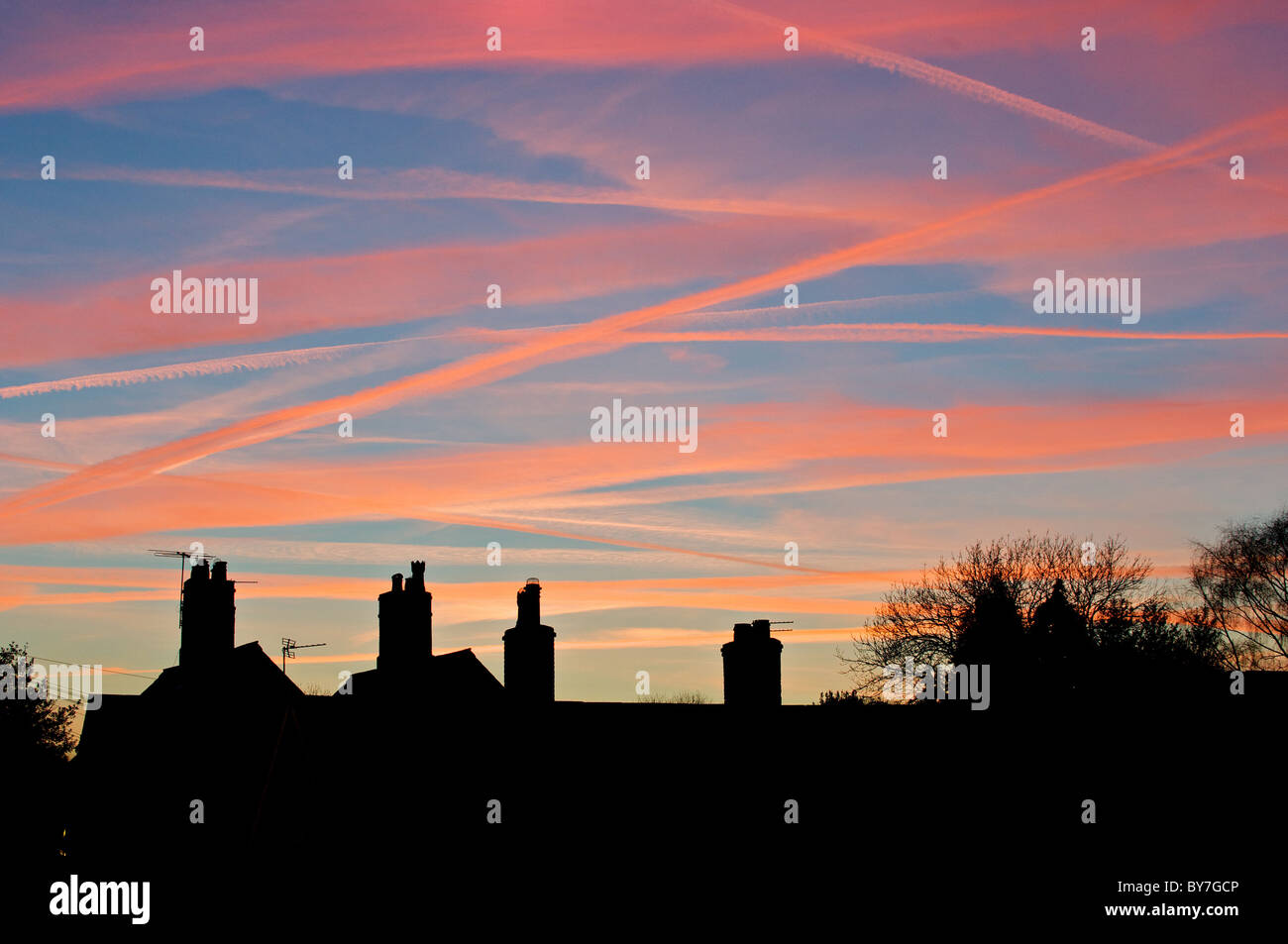 Aircraft contrails exaggerated by the setting sun and red sky above these Cheshire chimney tops - Stock Image