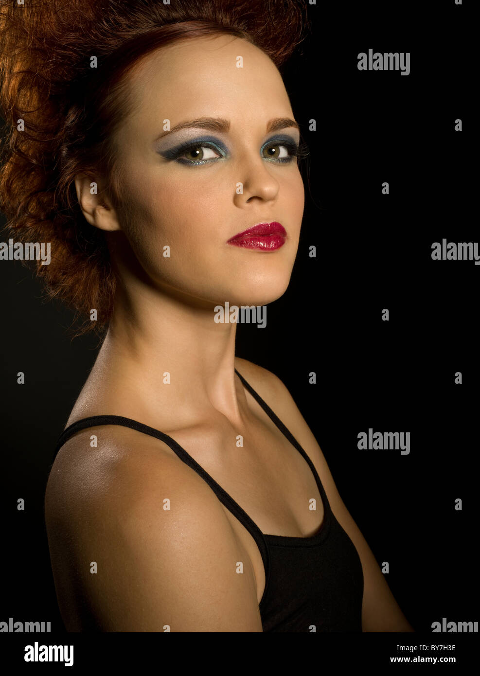 Fiery red head with eyeshadow and lipstick - Stock Image